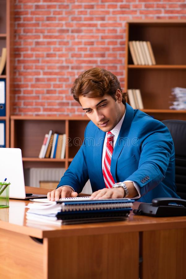 The young handsome employee sitting in the office. Young handsome employee sitting in the office royalty free stock image