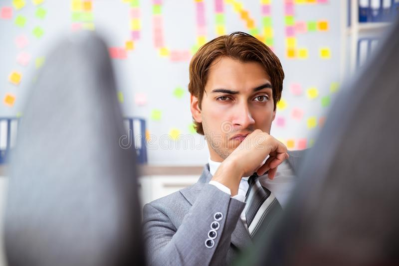 The young handsome employee sitting at the office. Young handsome employee sitting at the office stock image