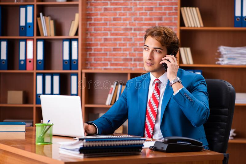The young handsome employee sitting in the office. Young handsome employee sitting in the office stock image