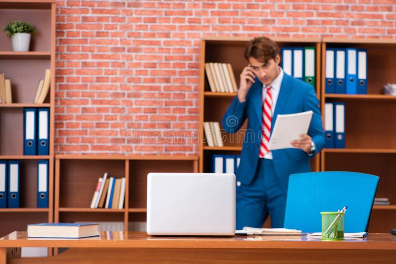 The young handsome employee sitting in the office. Young handsome employee sitting in the office stock images