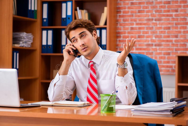 The young handsome employee sitting in the office. Young handsome employee sitting in the office stock photos