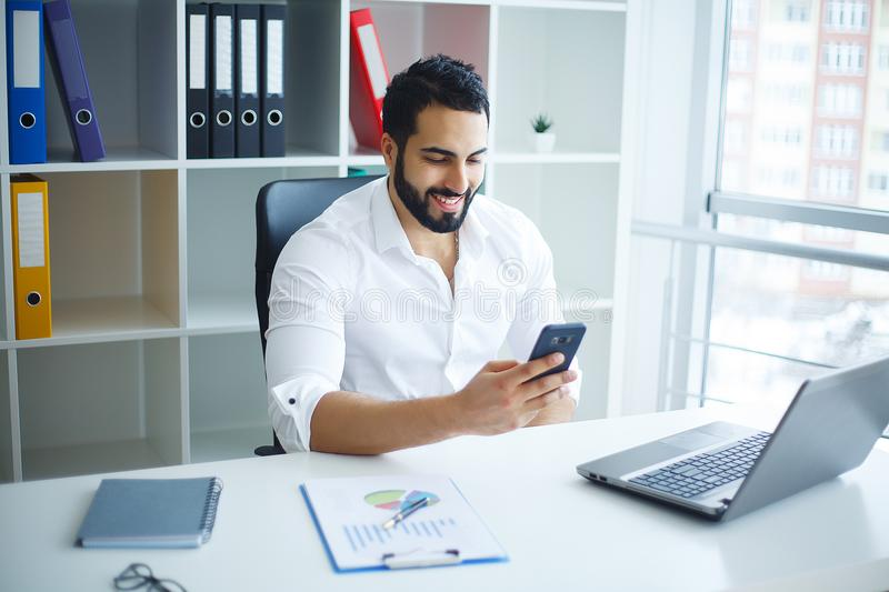 Young handsome entrepreneur sitting at desk and using laptop in. Office stock photography