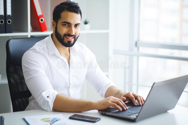 Young handsome entrepreneur sitting at desk and using laptop in. Office royalty free stock images