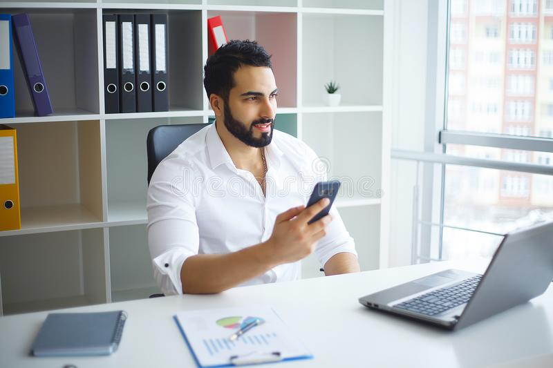 Young handsome entrepreneur sitting at desk and using laptop in. Office stock images