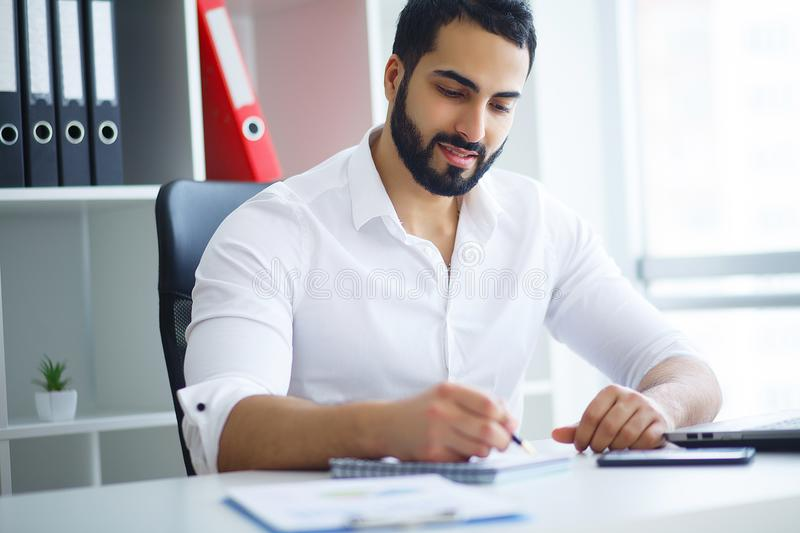 Young handsome entrepreneur sitting at desk and using laptop in. Office royalty free stock photo