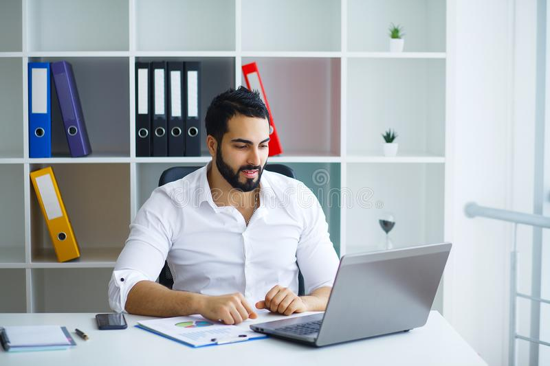 Young handsome entrepreneur sitting at desk and using laptop in. Office royalty free stock photos