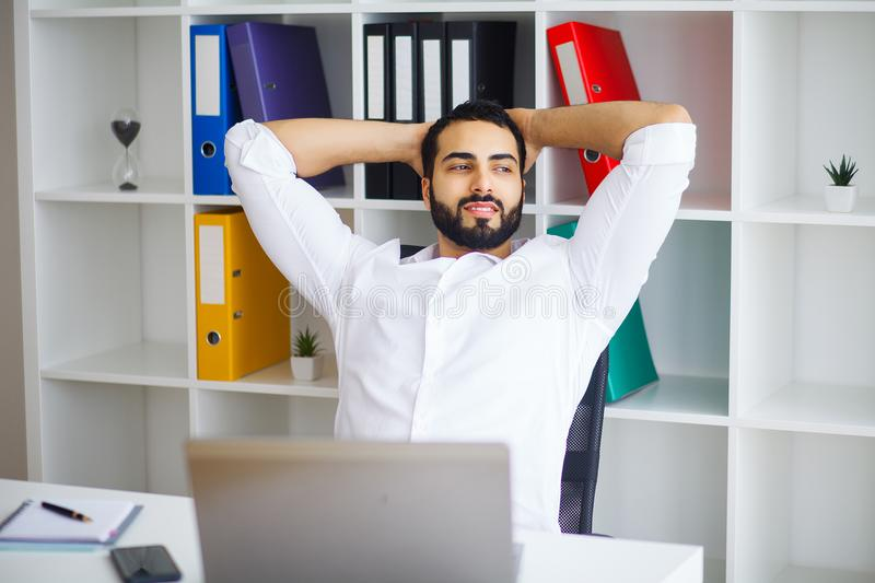 Young handsome entrepreneur sitting at desk and using laptop in. Office stock image