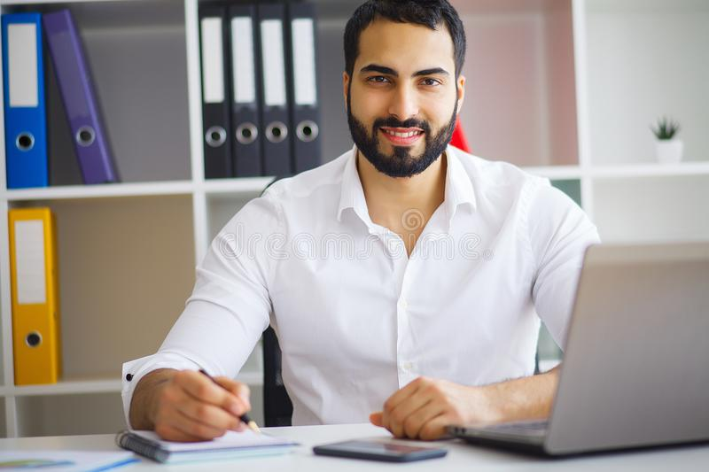 Young handsome entrepreneur sitting at desk and using laptop in. Office stock photo