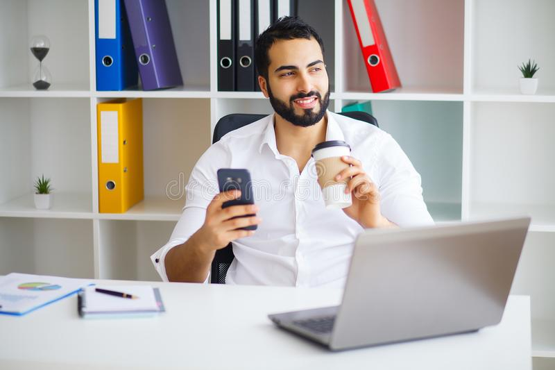 Young handsome entrepreneur sitting at desk and using laptop in. Office royalty free stock photography