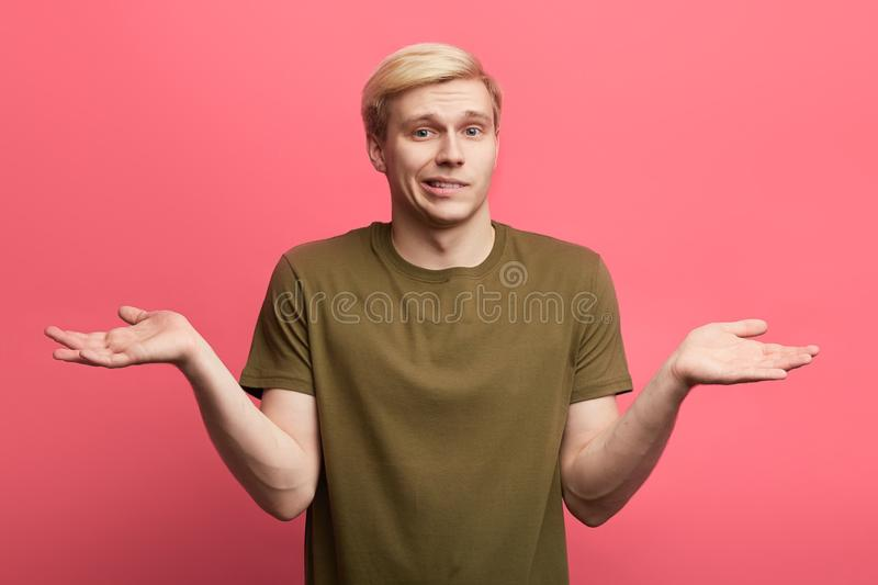 Young handsome fair-haired Caucasian man shrugging shoulders. Nothing for it. Puzzled guy doesn`t know the answer of the question royalty free stock photography