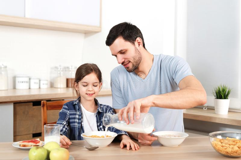 Young handsome father pours milk in bowl with flakes, prepares breakfast for small child, sit together at kitchen, have stock photo