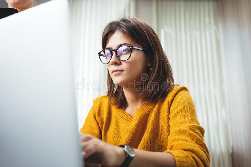 Young handsome female worker using modern laptop stock images