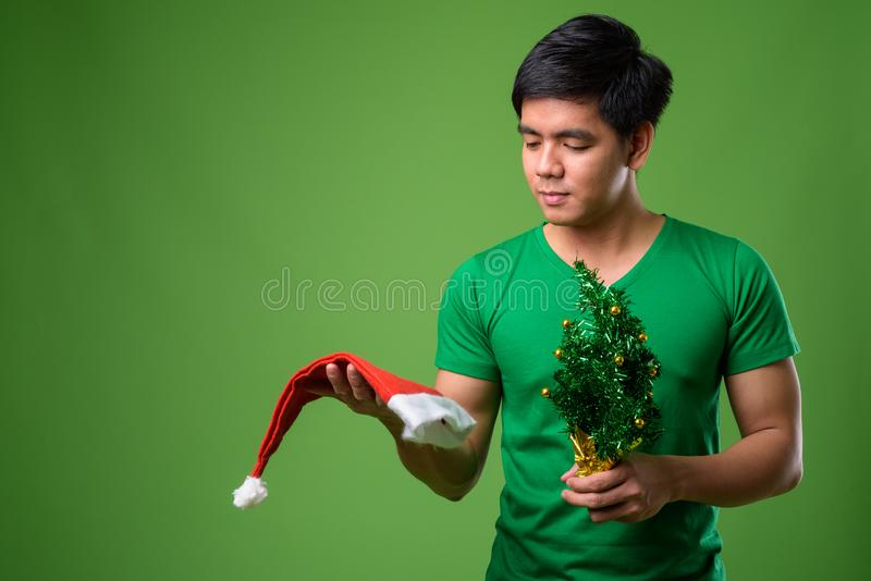 Young handsome Filipino man ready for Christmas against green ba. Studio shot of young handsome Filipino man ready for Christmas against green background stock photo