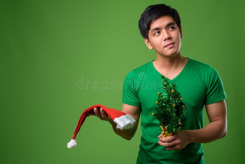 Young handsome Filipino man ready for Christmas against green ba. Studio shot of young handsome Filipino man ready for Christmas against green background royalty free stock photo