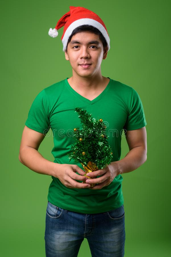 Young handsome Filipino man ready for Christmas against green ba. Studio shot of young handsome Filipino man ready for Christmas against green background royalty free stock photos