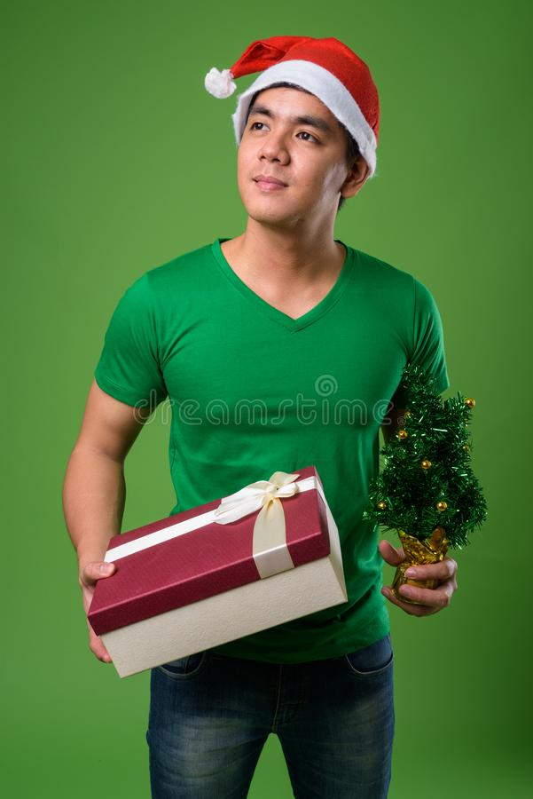 Young handsome Filipino man ready for Christmas against green ba. Studio shot of young handsome Filipino man ready for Christmas against green background royalty free stock photography