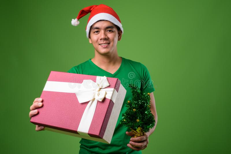 Young handsome Filipino man ready for Christmas against green ba. Studio shot of young handsome Filipino man ready for Christmas against green background stock photos