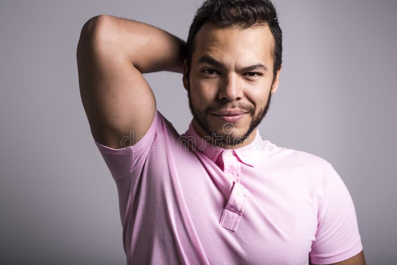 Young handsome fitness man in pink shirt, studio shot. royalty free stock image