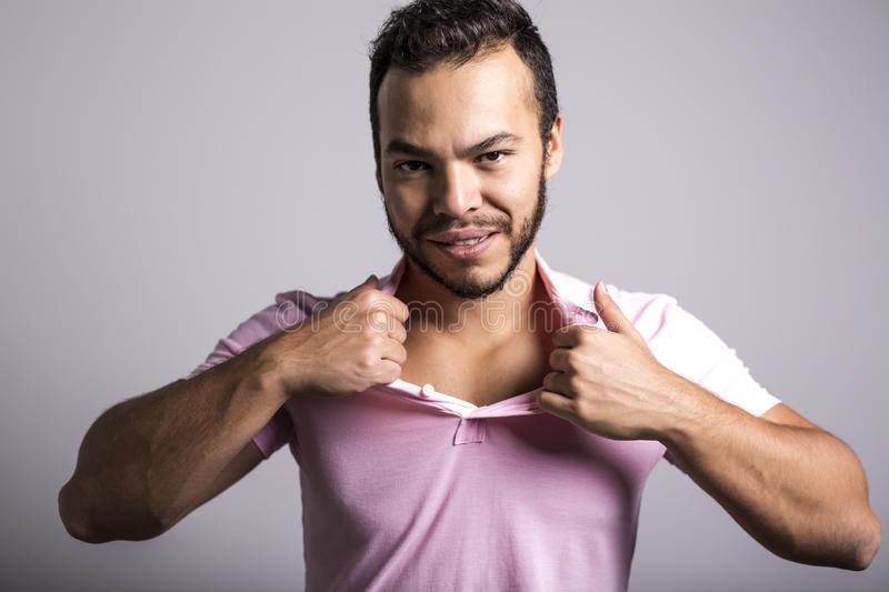 Young handsome fitness man in pink shirt, studio shot. stock photos