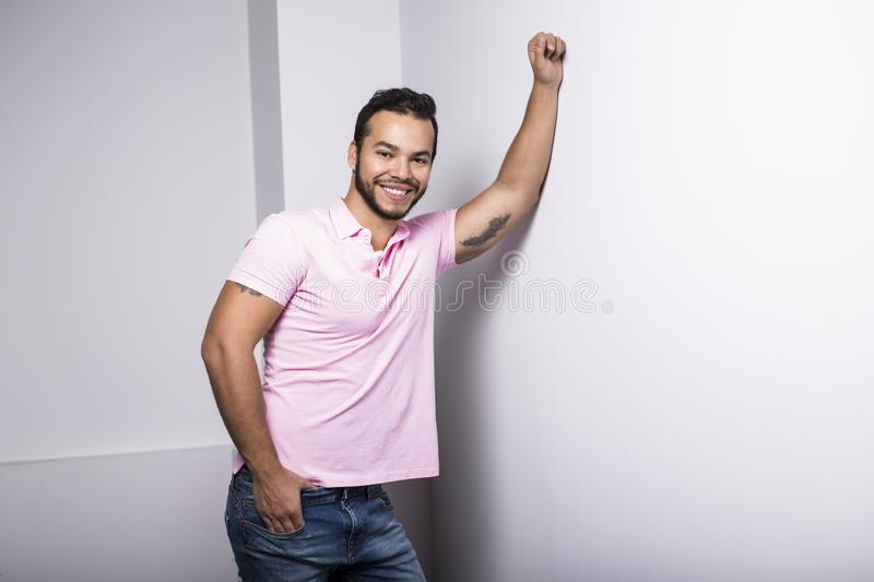Young handsome fitness man in pink shirt, studio shot. royalty free stock images