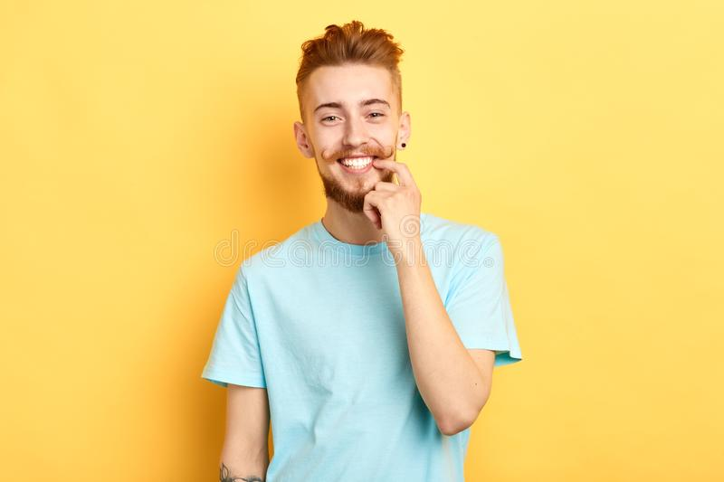 Young handsome guy with funny moustache showing and pointing at white teeth royalty free stock photography