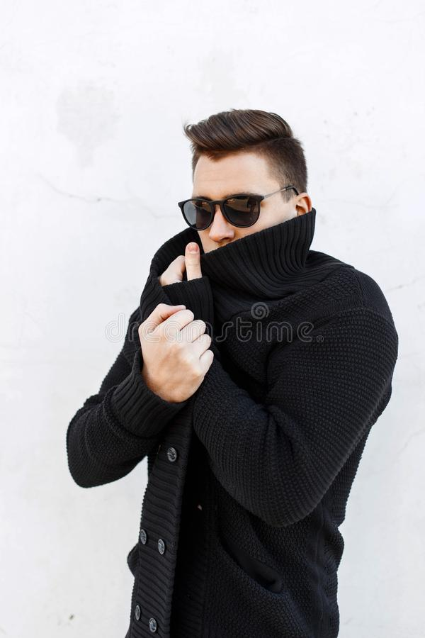 Young handsome guy with hair in a black sweater and sunglasses s. Tanding near a white wall stock photos