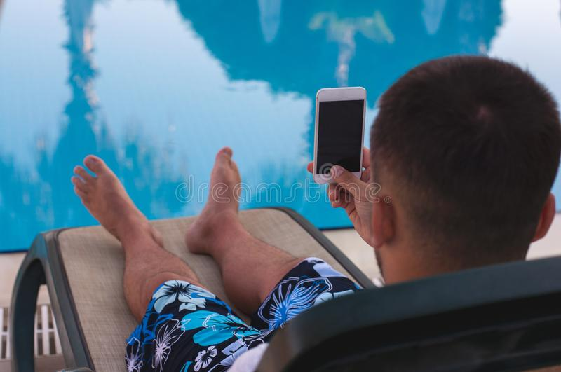 Young handsome guy lies on a deck chair near the pool and holds a smartphone in his hands. Selfie by the water. Photo for memory. Young handsome guy lies on a royalty free stock photography