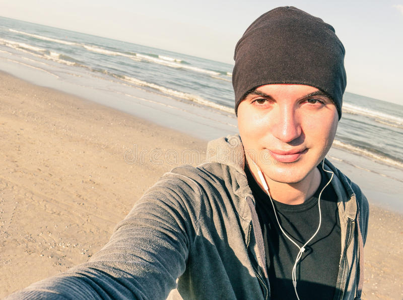Young handsome guy with male sport clothes taking selfie. On the beach in autumn season - Healthy lifestyle and fitness training concept - Tilted horizon royalty free stock images