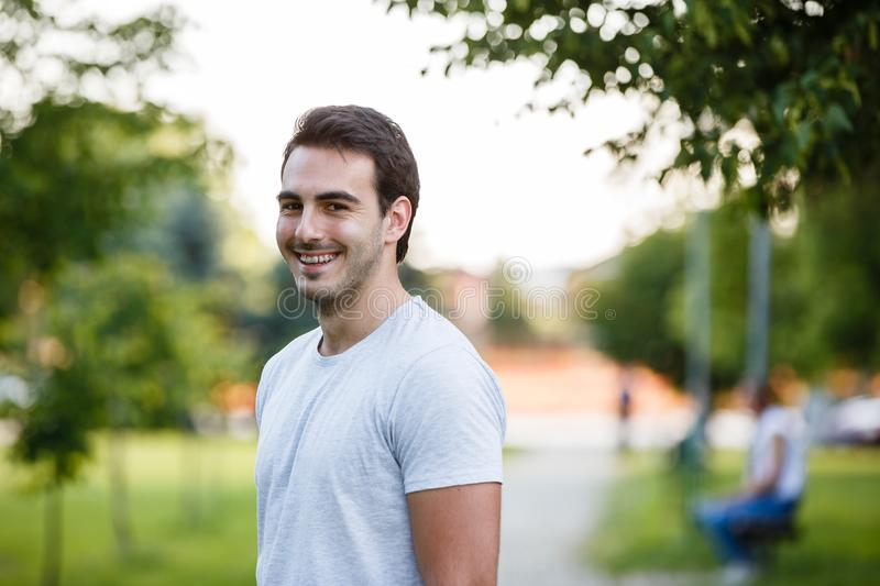 Young handsome guy in park standign and smiling stock images