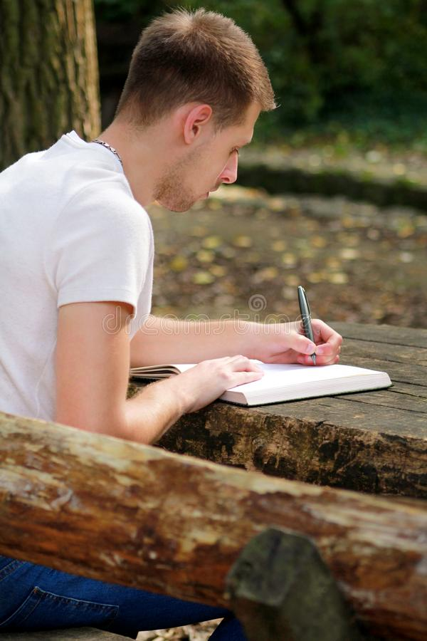 Young handsome guy sitting at wooden table, writing a book, doing homework, taking notes, learning, contemplating and writing. royalty free stock image