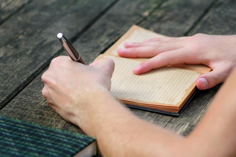 Young handsome guy sitting at wooden table, writing a book, doing homework, taking notes, learning, contemplating and writing. royalty free stock photography