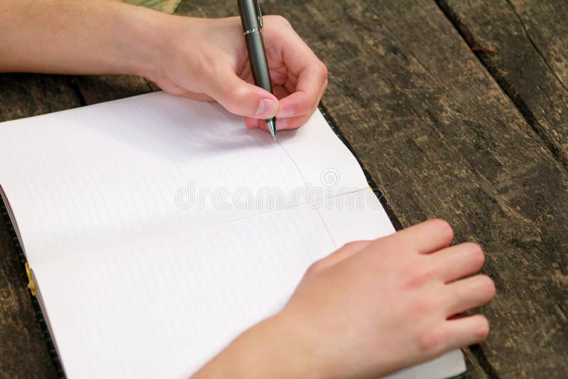 Young handsome guy sitting at wooden table, writing a book, doing homework, taking notes, learning, contemplating and writing. stock photo