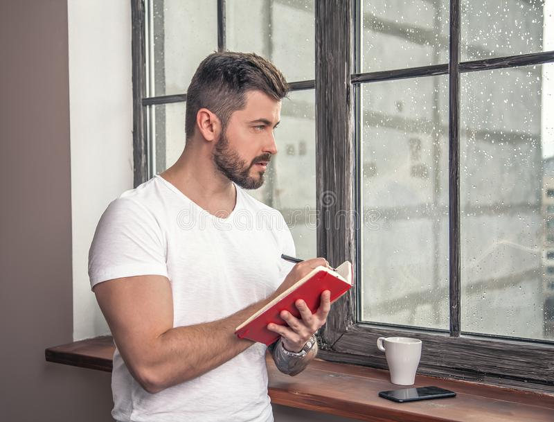 Young handsome guy is standing by the window with a cup go coffee, holding block note in his hand and making some notes thinking royalty free stock photos