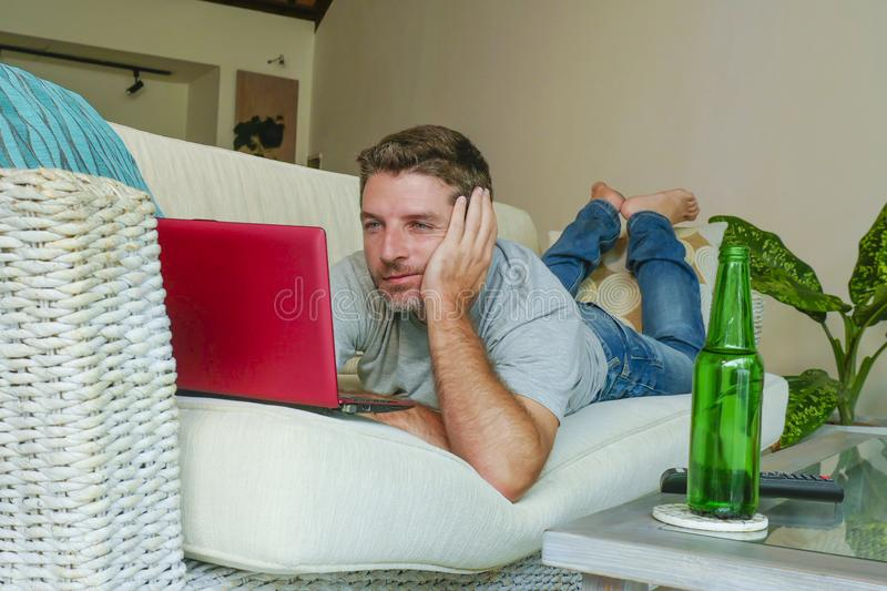 Young handsome happy man lying at home sofa couch working online with laptop computer using netbook relaxed comfortable with beer. Lifestyle indoors portrait of royalty free stock images