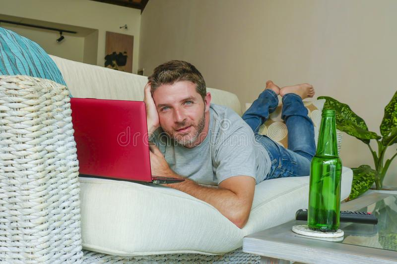 Young handsome happy man lying at home sofa couch working online with laptop computer using netbook relaxed comfortable with beer. Lifestyle indoors portrait of stock photography