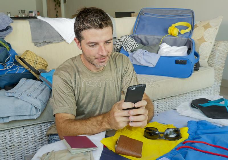 Young handsome and happy man packing travel suitcase at home sofa couch using mobile phone organizing holidays trip booking online royalty free stock image