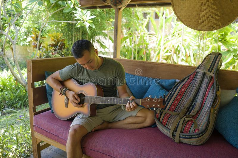 Young handsome and happy mixed ethnicity man in hipster style chilling outdoors playing guitar relaxed at tranquil tropical garden royalty free stock photos