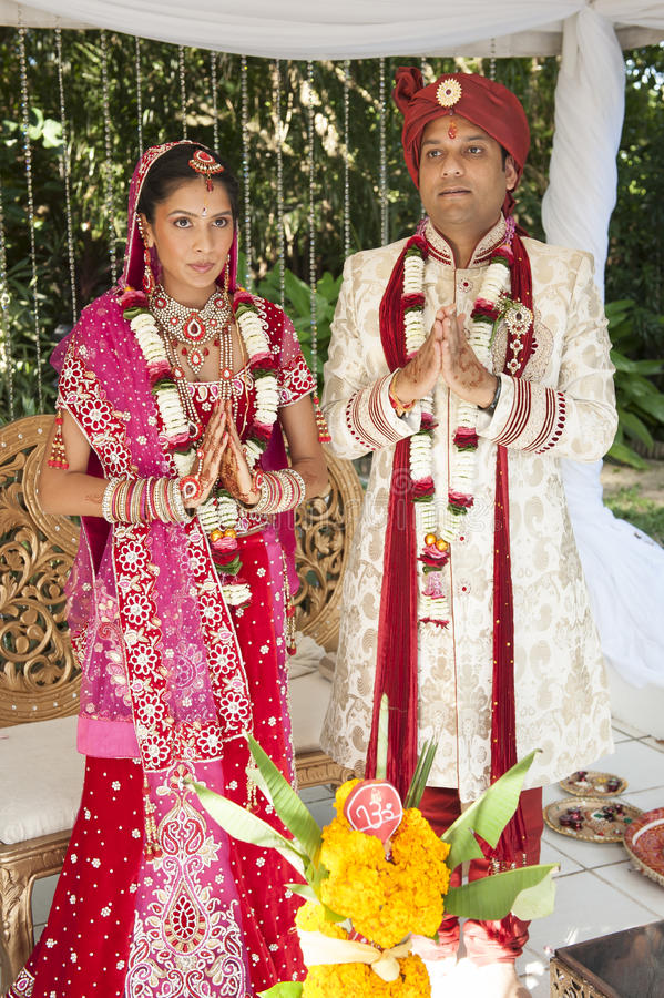 Young handsome Hindu bridal couple in traditional attire with wedding ceremony make up. Holding hands in prayer stock photo