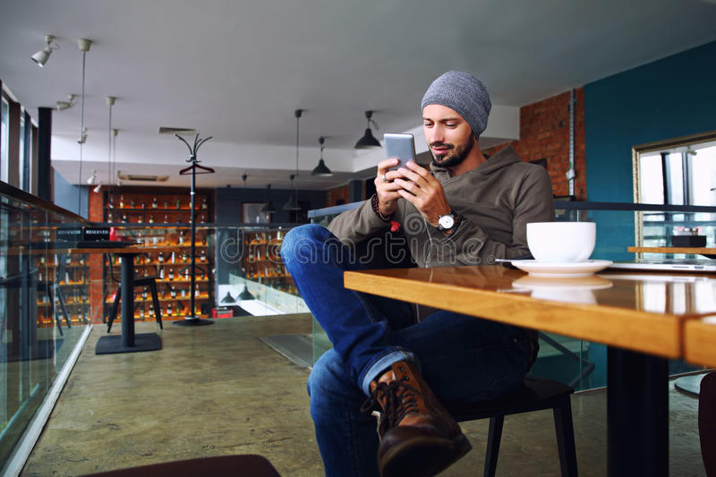 Young handsome hipster guy with beard texting with his mobile phone at the bar and having a cappuccino. stock photo
