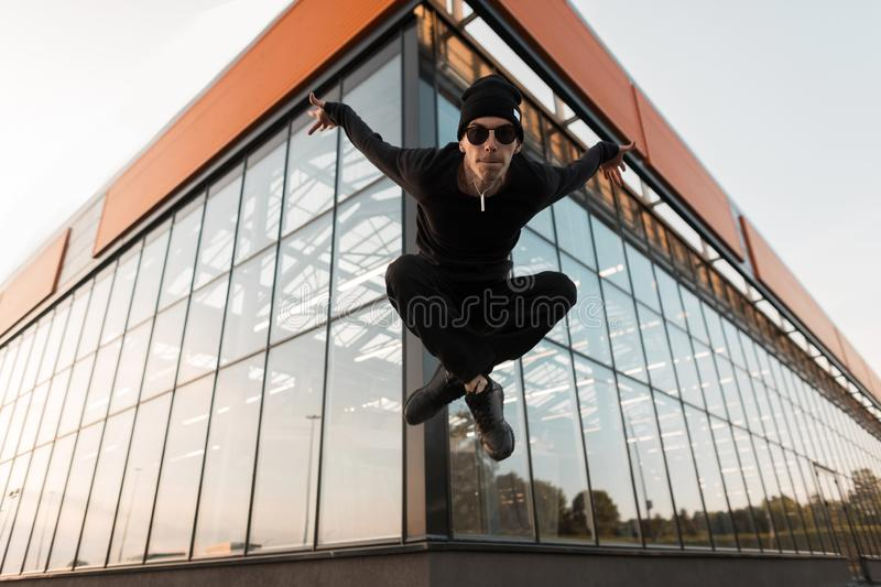Young handsome hipster man in black fashionable clothes in a stylish hat in fashionable sneakers in sunglasses is jumping. Near a glass building on a summer day royalty free stock image