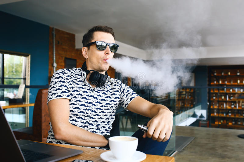 Young handsome hipster man insunglasse sitting in cafe with a cup of coffee, vaping and releases a cloud of vapor stock photo