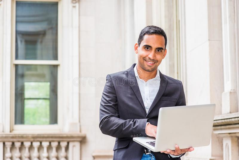 Young Handsome Hispanic American college student studying in New. York, wearing black blazer, white shirt, sitting inside old office building on campus, working royalty free stock photos