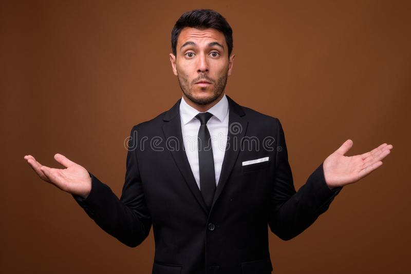 Young handsome Hispanic businessman against brown background. Studio shot of young handsome Hispanic businessman wearing suit against brown background stock photography