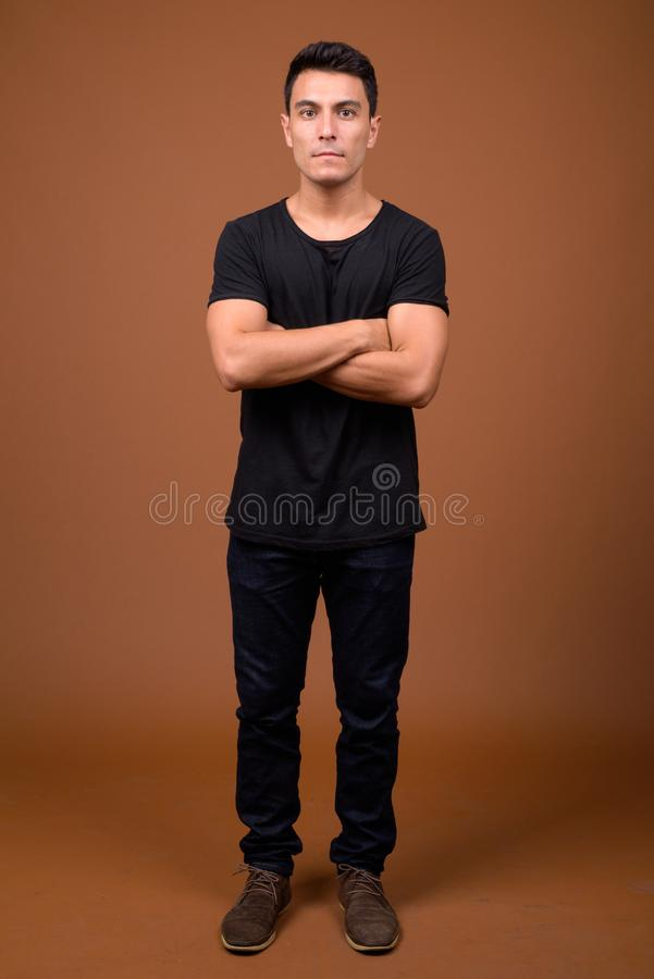 Young handsome Hispanic man against brown background. Studio shot of young handsome Hispanic man wearing black shirt against brown background stock photography