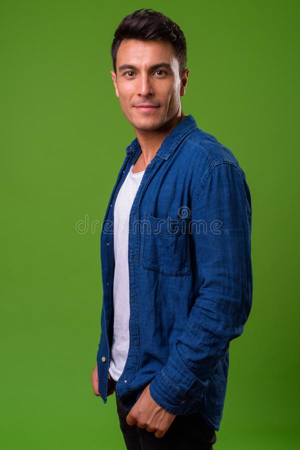 Young handsome Hispanic man against green background. Studio shot of young handsome Hispanic man against chroma key with green background stock photography