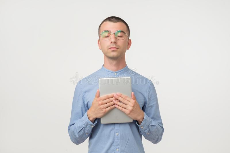 Young handsome hispanic man in glasses standing with closed eyes holding tablet device stock images