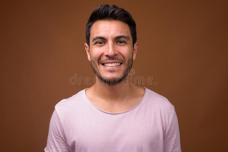 Young handsome Hispanic man smiling against brown background. Studio shot of young handsome Hispanic man wearing pink shirt against brown background stock image