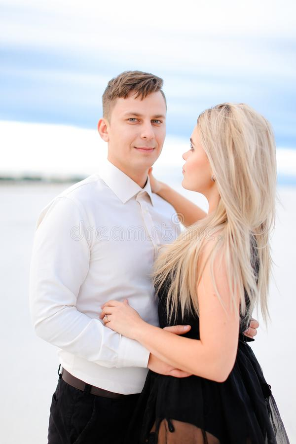 Young handsome husband in white shirt hugging wife wearing black dress in winter steppe. stock image