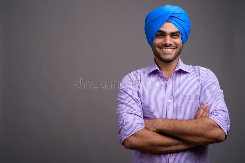 Young handsome Indian businessman wearing turban against gray ba royalty free stock photo