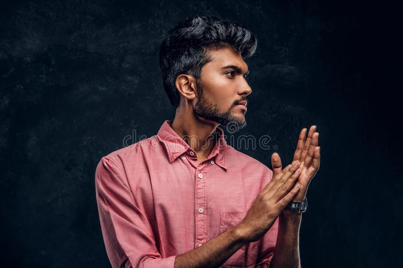 Young handsome Indian guy in a stylish pink shirt rubs his hands and looks sideways. Studio photo against a dark textured wall royalty free stock image